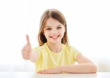 Bella bambina a casa che mostra i pollici su Fotografie Stock