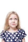 Bella bambina che considera scettico qualcosa isolato Fotografia Stock