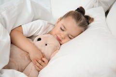 Bella bambina che dorme con il giocattolo a letto bedtime fotografie stock libere da diritti
