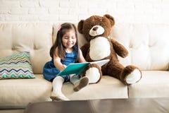 Bella bambina che legge un libro con l'orsacchiotto fotografia stock libera da diritti