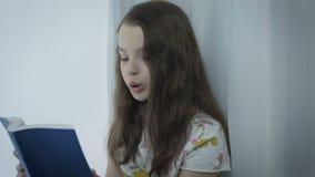 Bella bambina che legge un libro interessante dalla finestra stock footage