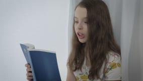 Bella bambina che legge un libro interessante dalla finestra video d archivio