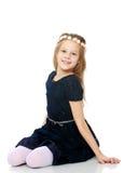 Bella bambina che posa seduta sul pavimento fotografia stock