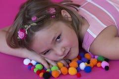 Bella bambina che si riposa sui poms variopinti del pom immagine stock libera da diritti