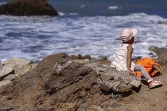 Bella bambina che si siede su una roccia e che esamina il DIS fotografie stock