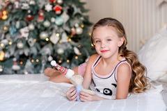 Bella bambina che si siede vicino all'albero di Natale Immagine Stock