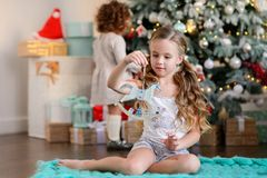Bella bambina che si siede vicino all'albero di Natale Fotografia Stock