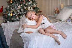 Bella bambina che si siede vicino all'albero di Natale Fotografia Stock Libera da Diritti