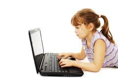 Bella bambina che si trova sul pavimento con un computer portatile Fotografia Stock Libera da Diritti