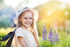 Bella bambina con capelli biondi che sorride felicemente sulla natura Immagini Stock