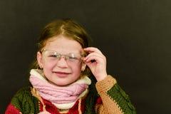 Bella bambina con i vetri su fondo nero Ragazza sveglia divertente con i vetri La piccola ragazza porta il maglione variopinto Immagine Stock Libera da Diritti