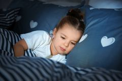 Bella bambina con l'aggeggio a letto alla notte bedtime fotografia stock