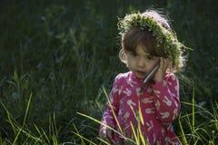 Bella bambina con la corona della testa di fiori e parlare sul suo telefono cellulare nel parco Immagine Stock