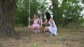 Bella bambina con la sua guida della madre su un'oscillazione, nel parco, in natura video d archivio
