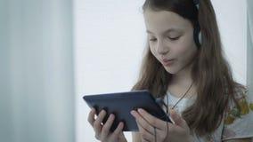 Bella bambina con le cuffie che guarda i video divertenti sulla compressa archivi video
