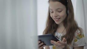 Bella bambina con le cuffie che guarda i video divertenti sulla compressa e sui sorrisi video d archivio