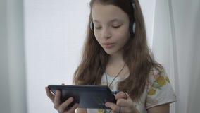 Bella bambina con le cuffie che guarda i video divertenti sulla compressa e sulle risate archivi video