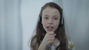 Bella bambina in cuffie che canta emozionalmente canzone archivi video