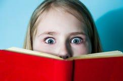 Bella bambina di colpo in testa che si nasconde dietro il libro, sembrante spaventato Fronte, espressioni facciali, emozioni, rea Fotografia Stock