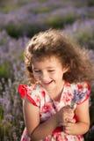 Bella bambina di risata felice con il mazzo dei fiori nel giacimento della lavanda immagine stock