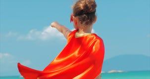 Bella bambina nel costume del supereroe, vestito in un mantello rosso e nella maschera dell'eroe Giochi sui precedenti archivi video