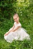 Bella bambina in un vestito bianco che posa nell'erba Immagini Stock Libere da Diritti