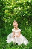 Bella bambina in un vestito bianco che posa nell'erba Fotografia Stock