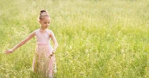 Bella bambina in un vestito bianco che posa nell'erba Fotografie Stock Libere da Diritti