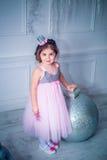 Bella bambina in vestito che decora l'albero di Natale Isolato su bianco Fotografia Stock