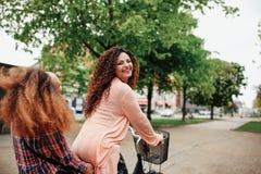 Bella bicicletta di guida della donna con il suo amico Immagini Stock