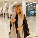 Bella bionda alla moda graziosa della giovane donna in un cappotto alla moda di autunno con una sciarpa d'annata che fa spesa in  immagine stock libera da diritti