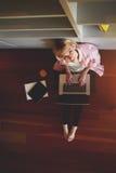 Bella bionda in camicia rosa che si siede sul pavimento con un computer sul suo rivestimento Immagine Stock