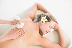 Bella bionda che gode di un massaggio di erbe della compressa Immagine Stock