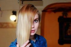 Bella bionda che guarda seriamente nella macchina fotografica, mano a capelli Fotografie Stock