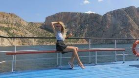 Bella bionda con capelli lunghi che fluttuare nel vento si siede sul battello da diporto che è nel mare stock footage