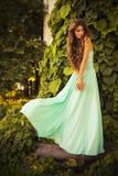 Bella bionda con i capelli ricci lunghi in un vestito da sera lungo nell'elettricità statica all'aperto vicino a retro costruzion Immagini Stock Libere da Diritti