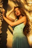 Bella bionda con i capelli ricci lunghi in un vestito da sera lungo nell'elettricità statica all'aperto vicino a retro costruzion Immagine Stock