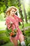 Bella bionda con il canestro dei fiori nell'oscillazione frondosa Fotografie Stock Libere da Diritti