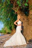 Bella bionda della sposa sotto l'albero alla sponda del fiume su un bea Fotografia Stock