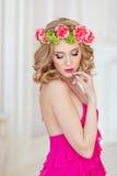 Bella bionda sexy esile in un vestito rosso ed in una corona del fiore fotografia stock