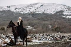 Bella bionda Viking in un capo nero a cavallo immagine stock