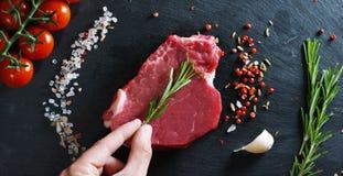 Bella bistecca succosa della carne fresca su una tavola con sale, rosmarini, aglio ed il pomodoro su un fondo nero, vista superio immagine stock libera da diritti