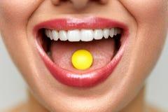 Bella bocca della donna con la pillola sulla lingua Ragazza che cattura medicina Fotografia Stock