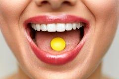 Bella bocca della donna con la pillola sulla lingua Ragazza che cattura medicina Fotografia Stock Libera da Diritti