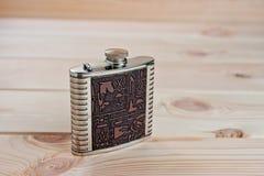 Bella boccetta del metallo per le bevande alcoliche con i disegni nello stile egiziano su un fondo di legno Immagine Stock Libera da Diritti