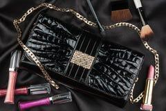 Bella borsa dalla pelle verniciata e dai cosmetici che si trovano sulla s nera Fotografia Stock