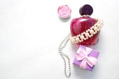 Bella bottiglia trasparente di vetro rosa di profumo femminile decorata con le perle bianche e una candela sotto forma di smal bl Immagini Stock