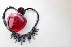 Bella bottiglia trasparente di vetro rossa di profumo femminile che si trova sulla corda nera sotto forma di un cuore decorato co fotografia stock libera da diritti