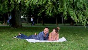Bella bugia delle coppie di Retty su erba verde messa su coperta bianca e conversazione sveglia sotto fogliame spesso stock footage