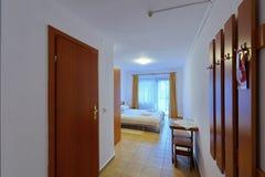 Bella camera di albergo spaziosa con il soffitto bianco di allungamento con un grande letto e le porte di legno Accogliente e mol Immagini Stock